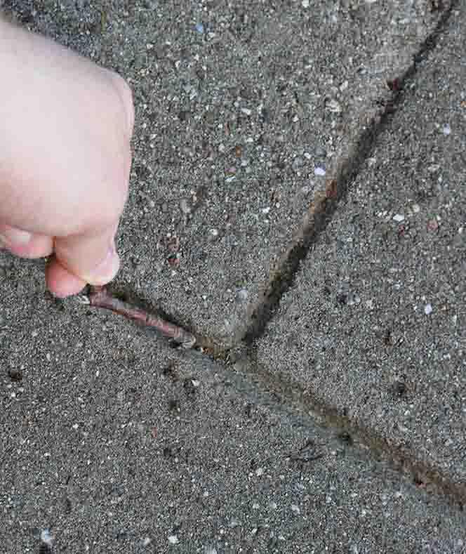 Losmaken van zand tussen tegels doe je met een stokje