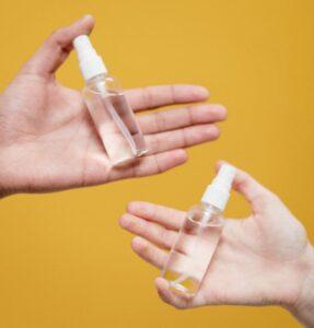 Foto van twee handen en twee flesjes alcohol