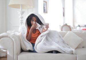 Foto van een vrouw die onder een deken op de bank ligt en in een papieren zakdoek haar neus snuit