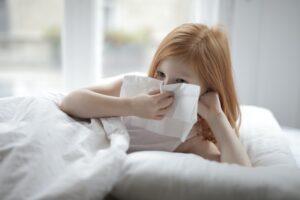 Foto van een meisje dat haar neus snuit in een papieren zakdoek.
