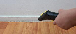 Foto van iemand die een stoomreiniger op een plint richt